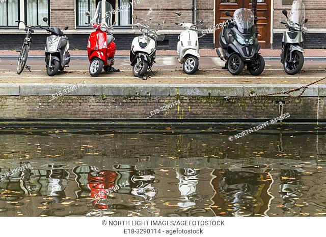 Netherlands, Amsterdam. Motorcycles, scooters and a bicycle parked in a line alongside a canal