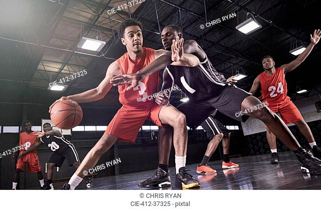 Young male basketball players playing on court in gymnasium