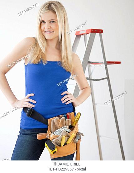 Portrait of young woman wearing tool belt