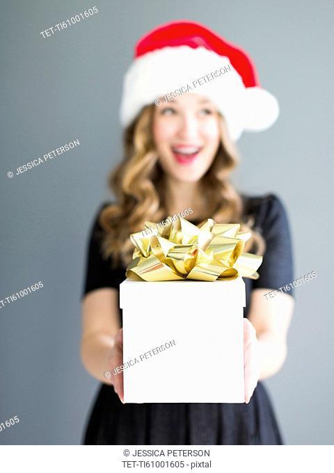 Studio portrait of woman wearing Santa hat holding gift
