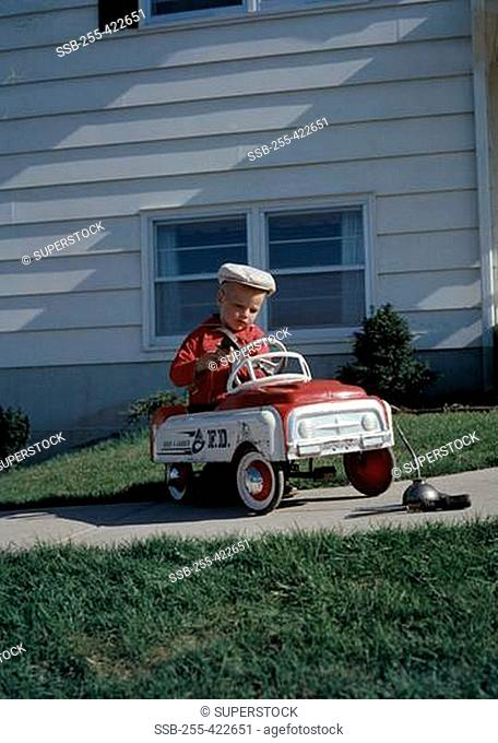 Boy playing with toy car in back yard