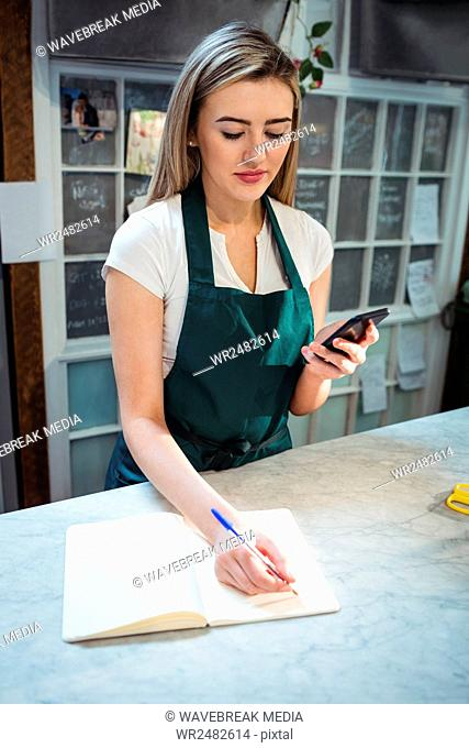 Female florist noting in diary while holding mobile phone