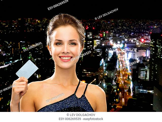 shopping, wealth, money, luxury and people concept - smiling woman in evening dress holding credit card over night city background