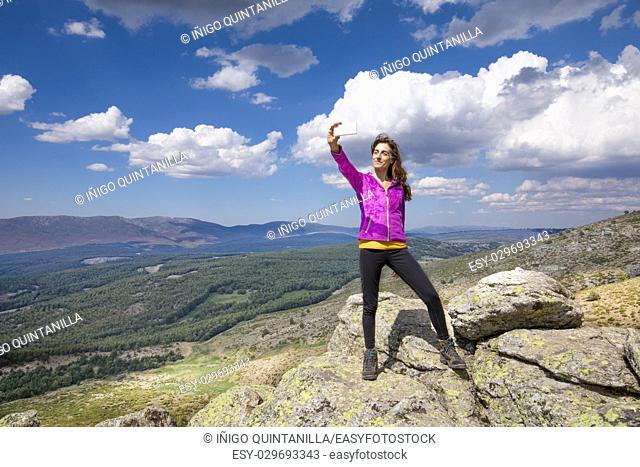 sport hiking or trekking woman with purple jacket, standing on rock peak, with mobile smart phone taking selfie photo picture