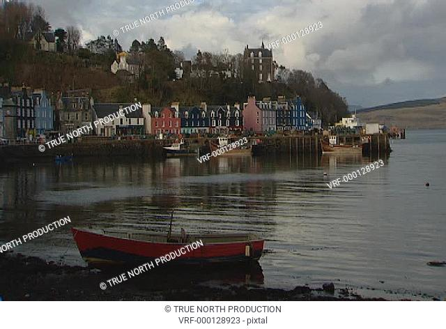 GV, Mwide shot of coastal village, rowing boat in foreground, calm sea, picture postcard, idyllic, peaceful. Mull, Scotland, UK
