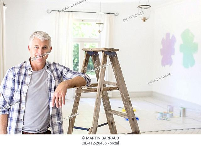 Older man smiling near ladder in livingroom