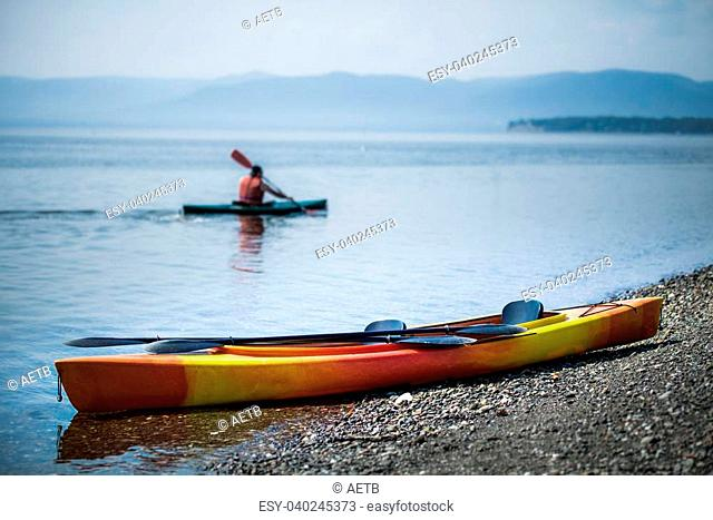 Orange and Yellow Kayak on the Sea Shore During a beautiful Day of Summer with Unrecognizable People Kayaking in the Background