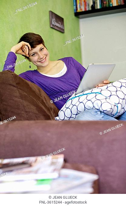 Young woman using iPad on couch