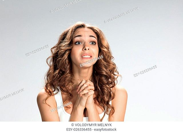 The Woman is looking imploring over gray background
