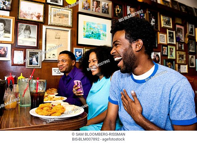 Friends eating and laughing in diner booth