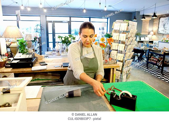 Female sales assistant wrapping candle at checkout in gift shop