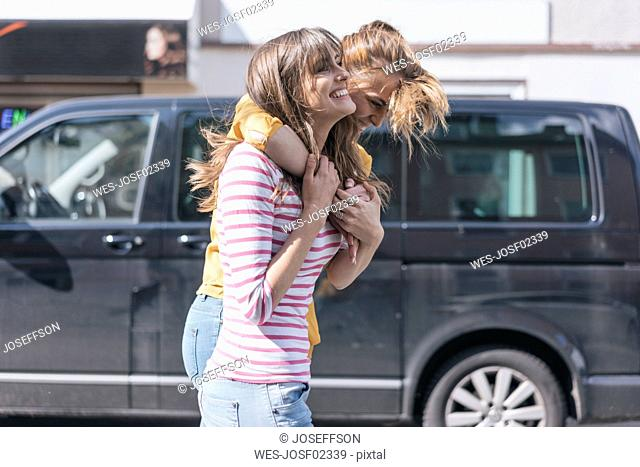 Two girlfriends having fun in the city, embracing