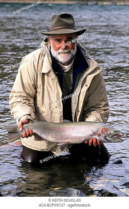 Flyfisherman holding Bulkley river steelhead prior to release, Smithers, British Columbia, Canada