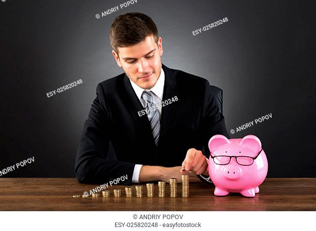 Portrait Of Young Businessman With Piggybank Stacking Coins On Desk