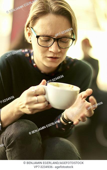woman looking at porcelain coffee cup in hands, sitting indoors in café, taking a break, Munich, Germany
