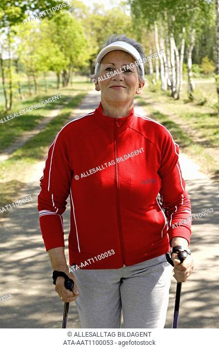 Older female person practicing nordic walking