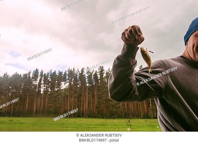 Fisherman holding small fish on hook