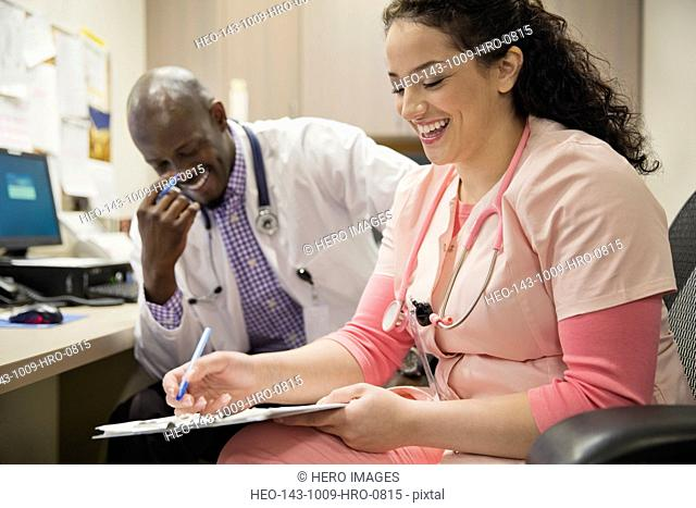 Happy medical professionals reviewing medical records together in clinic