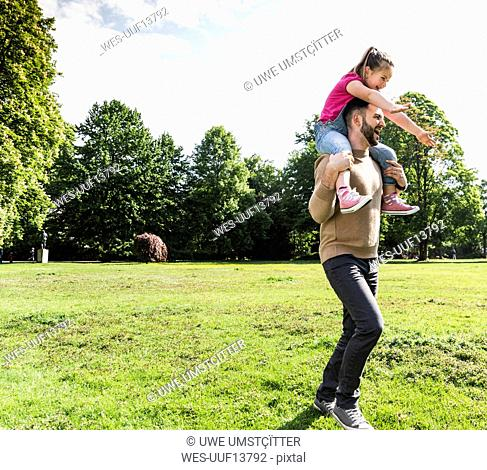 Happy father carrying daughter on shoulders in a park