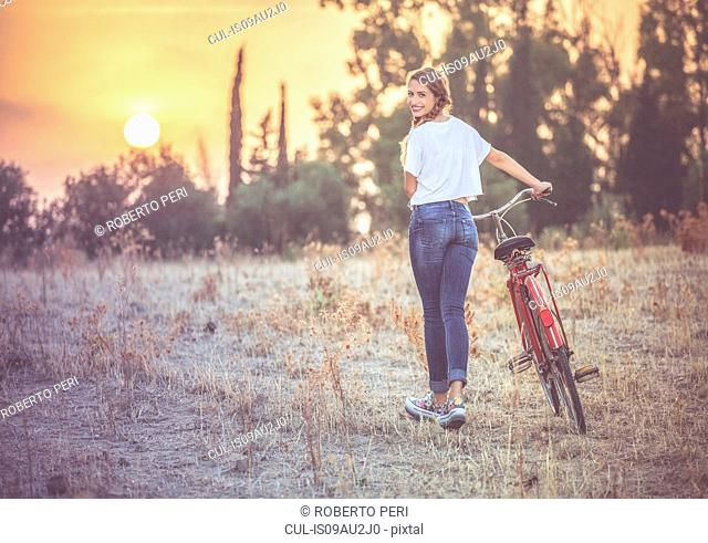 Girl walking her bike in countryside, Quartucciu, Sardinia, Italy