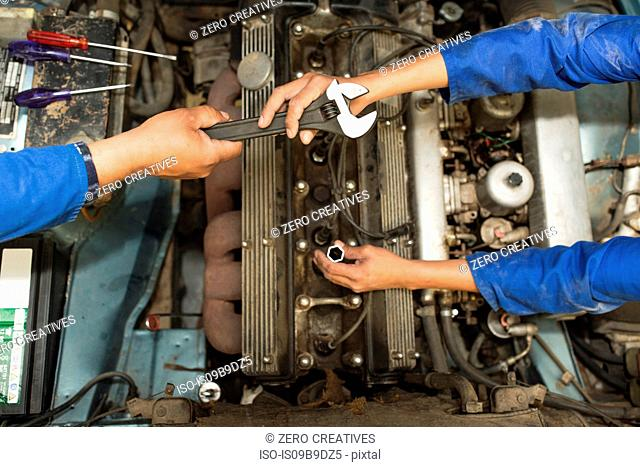 Overhead view of car mechanics hands and car engine in repair garage