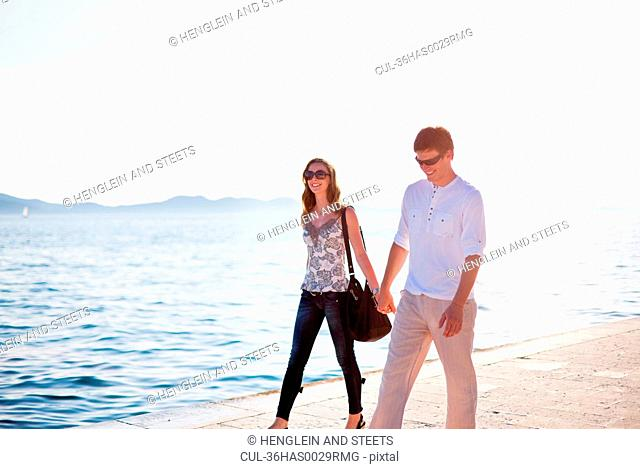 Couple walking hand-in-hand on pier