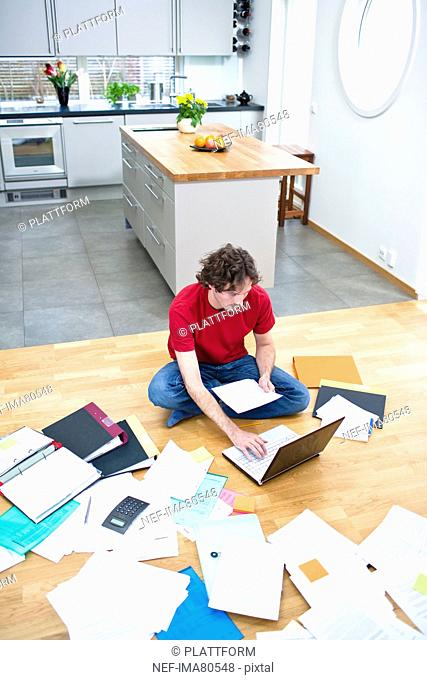 Elevated view of mid- adult man struggling with domestic paperwork