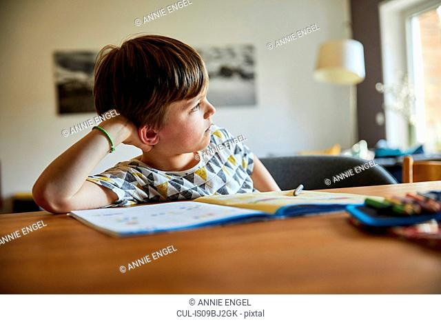 Portrait of boy resting on elbow looking away