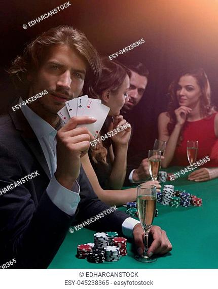 Poker players in casino with cards and chips on black background