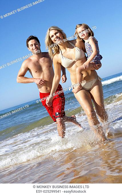 Family With Young Daughter Running Along Beach Together