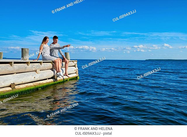 Young couple sitting on wooden pier, relaxing