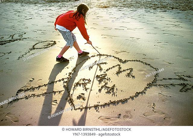 Young girl draws a love heart in the sand at the beach as the sun fades into an evening glow