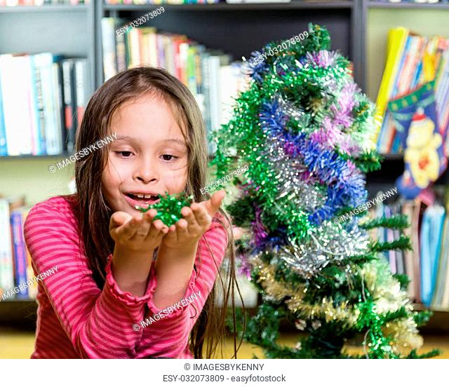 Young girl happily decorating Christmas tree, looking at tinsel in hands
