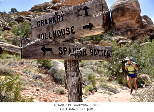 Female backpacker approaching trail sign at junction in The Maze in Canyonlands National Park, Moab, Utah, USA