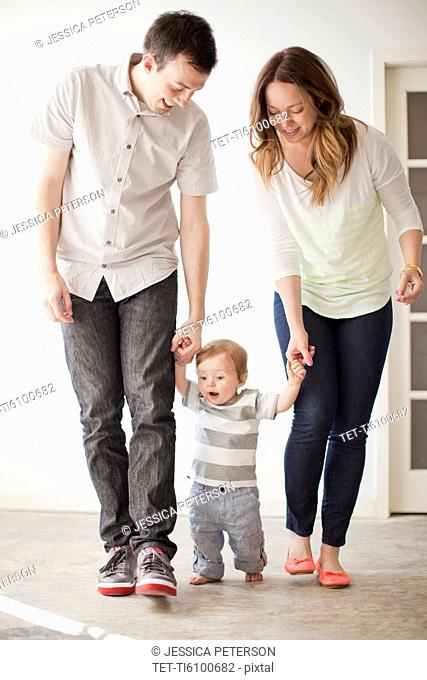 Young couple assisting baby boy 6-11 months in first steps