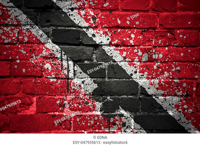 colorful painted national flag of trinidad and tobago on a old brick wall