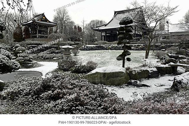30 January 2019, North Rhine-Westphalia, Düsseldorf: A thin layer of snow lies on the bell tower (l-r), the Buddhist temple and the Japanese Garden of the EKO...