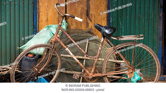 Rusted bicycle leaning against fishing nets, Siem Reap, Cambodia