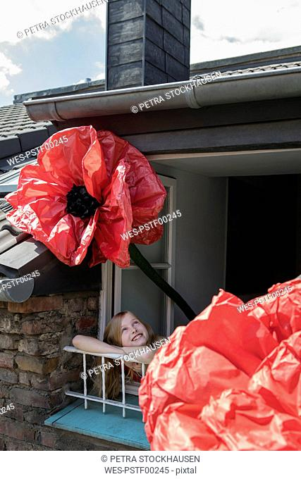 Happy girl with oversized redc artifical flower leaning out of window