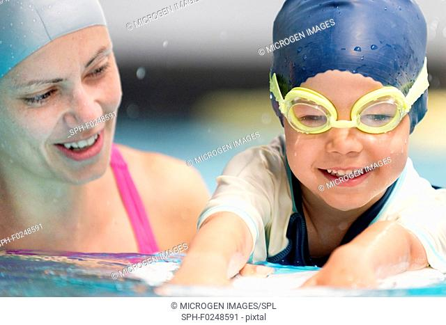 Happy little boy in swimming class with instructor