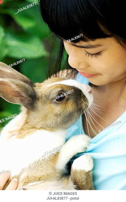 Close up of young girl holding rabbit