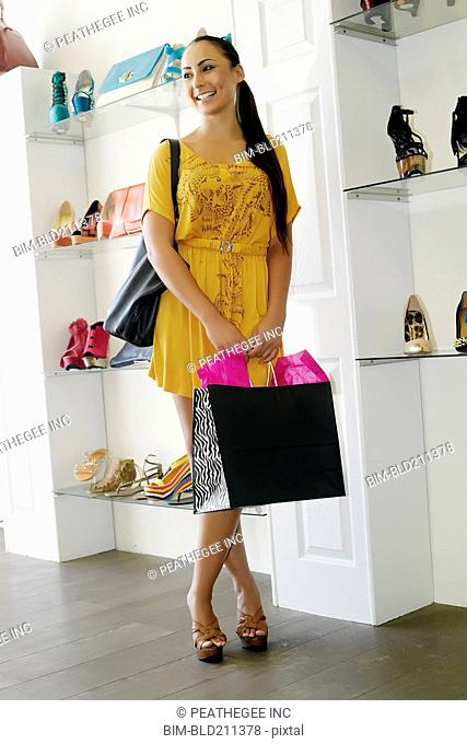 Mixed race woman shopping in shoe store