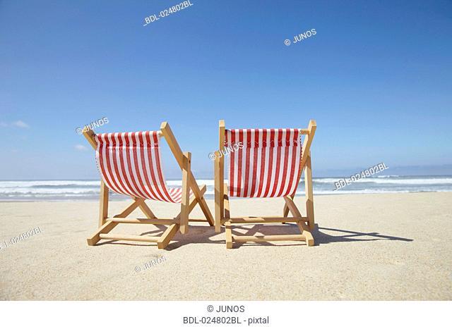 two sun loungers on sandy beach