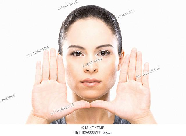 Young woman with hands in front of face