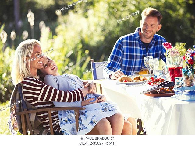 Smiling affectionate family enjoying lunch at sunny garden party patio table