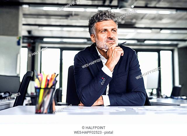 Confident mature businessman in office thinking