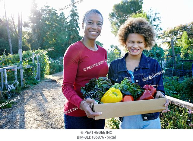 Mother and daughter gathering vegetables in community garden
