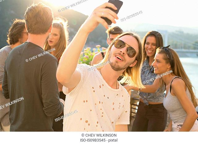 Young man taking selfie at waterfront roof terrace party, Budapest, Hungary