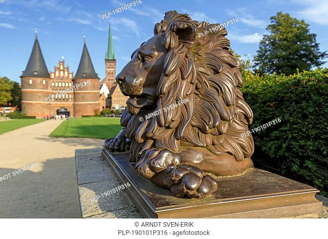 Lion statue in front of the Holstentor/ Holstein Gate in the Hanseatic town Lübeck, Schleswig-Holstein, Germany