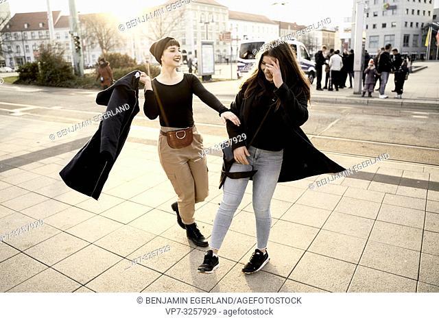 woman grabbing arm of friend on street, in city Cottbus, Brandenburg, Germany